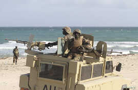 Peacekeepers from the African Union Mission in Somalia man weapons atop their Armoured Personnel Carrier after capturing the former private Elmaan seaport from al-Shabaab insurgents, 30km (19 miles) east of Mogadishu, September 4, 2012.