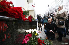 People pay tribute to passengers and crew members of Russian military Tu-154 plane crashed into the Black Sea, near a makeshift memorial outside the headquarters of the Alexandrov Ensemble, also known as the Red Army Choir, in Moscow, Dec. 25, 2016.