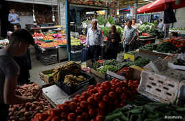 FILE - People shop at a vegetable and fruit market in Amman, Jordan, June 6, 2018. Climate change could drive up the prices of vegetables, according to a new study.