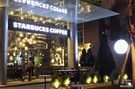 Workers prepare a Starbucks coffee shop for its opening in Vietnam's southern commercial hub of Ho Chi Minh City, July 30, 2013.