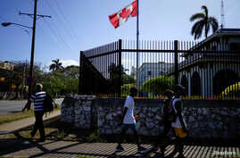 FILE PHOTO: People pass by the Canada's Embassy in Havana, Cuba, April 16, 2018.