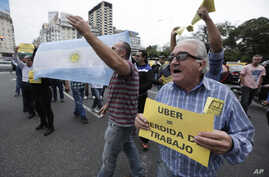 "A taxi driver holds a sign that says in Spanish ""Uber (equals) job loss"" as he and other cabbies block a main avenue in Buenos Aires, Argentina, April 12, 2016."