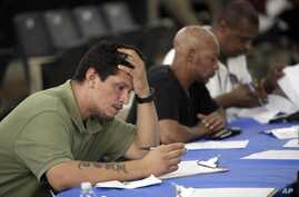 Job seekers fill out applications at a construction job fair in New York, August 21, 2012.