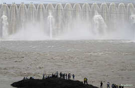 FILE - Picnickers stand in front of the overflowing Sardar Sarovar Narmada dam in Kavadia, 194 km (121 miles) south of the western Indian city of Ahmedabad, Aug. 10, 2012.