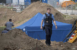 A police officer in Frankfurt, Germany, passes a blue tent that was set up over a 1.8-metric ton bomb of a type dropped by British bombers during World War II,  Aug. 30, 2017. City authorities in Frankfurt plan to evacuate more than 60,000 people fro