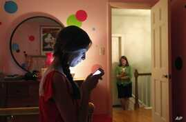 Teen girl, foreground, texts her mother as they pose for a photograph in LaGrange, Ill., May 24, 2012 (file photo).