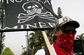 """FILE - A protester holds a sign that reads in Spanish """"No to mining"""" at a protest against Canada's gold and silver mining operations in northern El Salvador, outside Canada's Consulate office in San Salvador, May 21, 2007."""