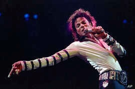 FILE - Michael Jackson leans, points and sings, dances and struts during the opening performance of his 13-city U.S. tour, in Kansas City, Mo.