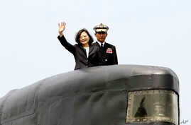 Taiwan's President Tsai Ing-wen, left, waves from a Zwaardvis-class submarine during a visit at Zuoying Naval base in Kaohsiung, southern Taiwan, March 21, 2017.