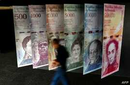 A man walks past banners showing banners depicting Venezuela's currency, the Bolivar, at the Central Bank of Venezuela in Caracas on Jan. 31, 2018.