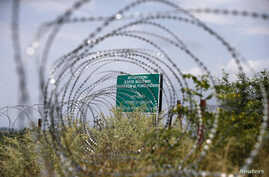 FILE - A warning sign behind a wire barricade erected by Russian and Ossetian troops along Georgia's de-facto border with its breakaway region of South Ossetia in the village of Khurvaleti, Georgia, July 14, 2015.