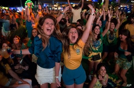 Soccer fans celebrate the second goal scored by Brazil striker Neymar, during a live broadcast at a World Cup viewing party at the Jockey Club, in Rio de Janeiro, Brazil, Thursday, June 12, 2014.