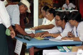 A voter signs his name to get a ballot sheet from an official of the Union Election Commission at a polling station in Yangon, Myanmar, April 1, 2017. Voting is underway in 19 by-elections in Myanmar, in the first test of the popularity of Aung San S