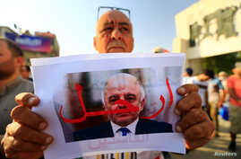 "A protester holds a picture of Iraqi Prime Minister Haider al-Abadi with ""Step Down"" written on it during a protest at Tahrir square in Baghdad, Iraq, July 27, 2018."