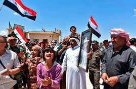 In this photo released by SANA, Syrians welcome government forces and police entering their village with a portrait of President Assad, national flags, and patriotic slogans, in northern countryside of Homs province, May 14, 2018.