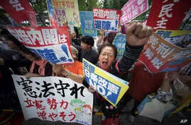 "Protesters gather in front of the Diet building in Tokyo, Sept. 28,2017, after Japanese Prime Minister Shinzo Abe dissolved the lower house of parliament, paving the way for a snap election. The banner at top in the center reads: ""Abe cabinet, go out"