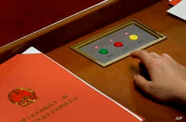 A delegate prepares to press buttons to vote on the draft resolutions during the closing session of the annual National People's Congress held in Beijing's Great Hall of the People on March 16, 2016.