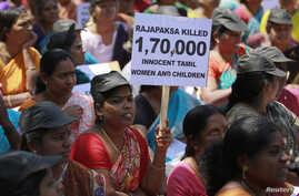 In a protest targeting Sri Lanka's President Mahinda Rajapaksa and alleged war crimes against Tamil civilians in his country, a demonstrator holds a placard in Mumbai, March 20, 2013.