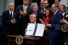 "President Donald Trump shows off the ""VA Mission Act"" during a signing ceremony in the Rose Garden of the White House, June 6, 2018, in Washington."