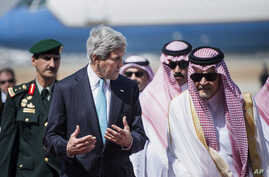 FILE - U.S. Secretary of State John Kerry, left, and Saudi Foreign Minister Saud al-Faisal walk together upon Kerry's arrival at King Abdulaziz International Airport in Jeddah, Saudi Arabia.