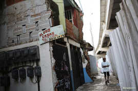 File -- A for rent sign hangs alongside a bridge of the Transolimpica BRT, an express road built through the Vila Uniao favela of Rio de Janeiro to join two Rio 2016 Olympic venues on August 12, 2016.