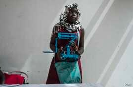 Rokyaha Cisse, 17, from  Dakar, holds up her team's robot at the 2017 Pan-African Robotics Competition in Dakar, Senegal. Their robot sends sounds into the ground, which detect the presence of metal. (R. Shryock/VOA)