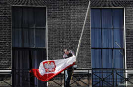 FILE - A man lowers the Polish national flag outside the Polish Embassy, in London, April 10, 2010.Economists warn that by leaving the EU, Britain may bring onto itself new restrictions on workers from mainland EU countries, thus causing possible lab
