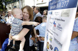 Jennifer Wonnacott holds her son Gavin as he points to a sign showing support of a measure requiring nearly all California school children to be vaccinated, at a news conference after the bill was signed by Gov. Jerry Brown, June 30, 2015, in Sacrame