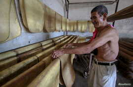 FILE- A man works inside a rubber factory at Raman district in the southern province of Yala, Thailand. Thailand's junta has approved $1.3 billion in rural subsidies, akin to the populist policies of the government it ousted, to appease disgruntled a