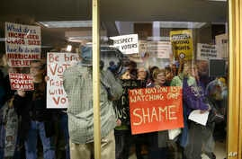 Protestors gather outside a press conference room during a special session at the North Carolina Legislature in Raleigh, N.C., Dec. 15, 2016. Republicans called their own special session to weigh legislation, some of which threatens the incoming Dem