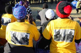 Supporters wearing t-shirts with a photo of former President Robert Mugabe, left,, at an election rally in Masvingo, Zimbabwe, July 14, 2018.