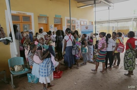 Women wait outside the family clinic. Jhpiego, a non-profit health organization, has folded screening into HIV-related health services, Boane, Mozambique, Nov. 20, 2014. (Gillian Parker/VOA)