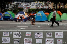 A protester draws on a main road in the occupied areas outside government headquarters in Hong Kong's Admiralty, Friday, Oct. 10, 2014. A pro-democracy protest that has blocked main roads in Hong Kong for almost two weeks could drag on for days yet,