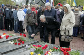 People lay flowers at a memorial bearing the names of victims of the Chernobyl nuclear accident, during a commemoration of the disaster's 30th anniversary, in Kyiv, Ukraine, April 26, 2016.