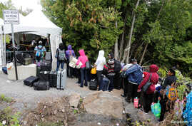 A line of asylum seekers who said they were from Haiti wait to enter into Canada from Roxham Road in Champlain, New York, Aug. 7, 2017.