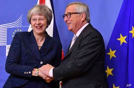 European Commission President Jean-Claude Juncker, right, greets British Prime Minister Theresa May at EU headquarters in Brussels, Nov. 24, 2018.