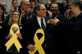 Newly appointed Catalan president Quim Torra, center, holds a yellow ribbon in support of Catalonian politicians who have been jailed on charges of sedition, at the end of a parliamentary vote session in Barcelona, Spain, May 14, 2018.