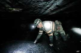 FILE - Coal miner Scott Tiller crawls through an underground coal mine roughly 40 inches high, May 11, 2016, in Welch, W.Va., about 60 miles from a coal mine in Clear Creek where three people missing since the weekend were found alive.