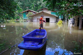 FILE - A boy catches fish in an area affected by floods in Yala province, southern Thailand, Jan. 21, 2017. Flooding in the northern and eastern regions have killed at least 23 people.