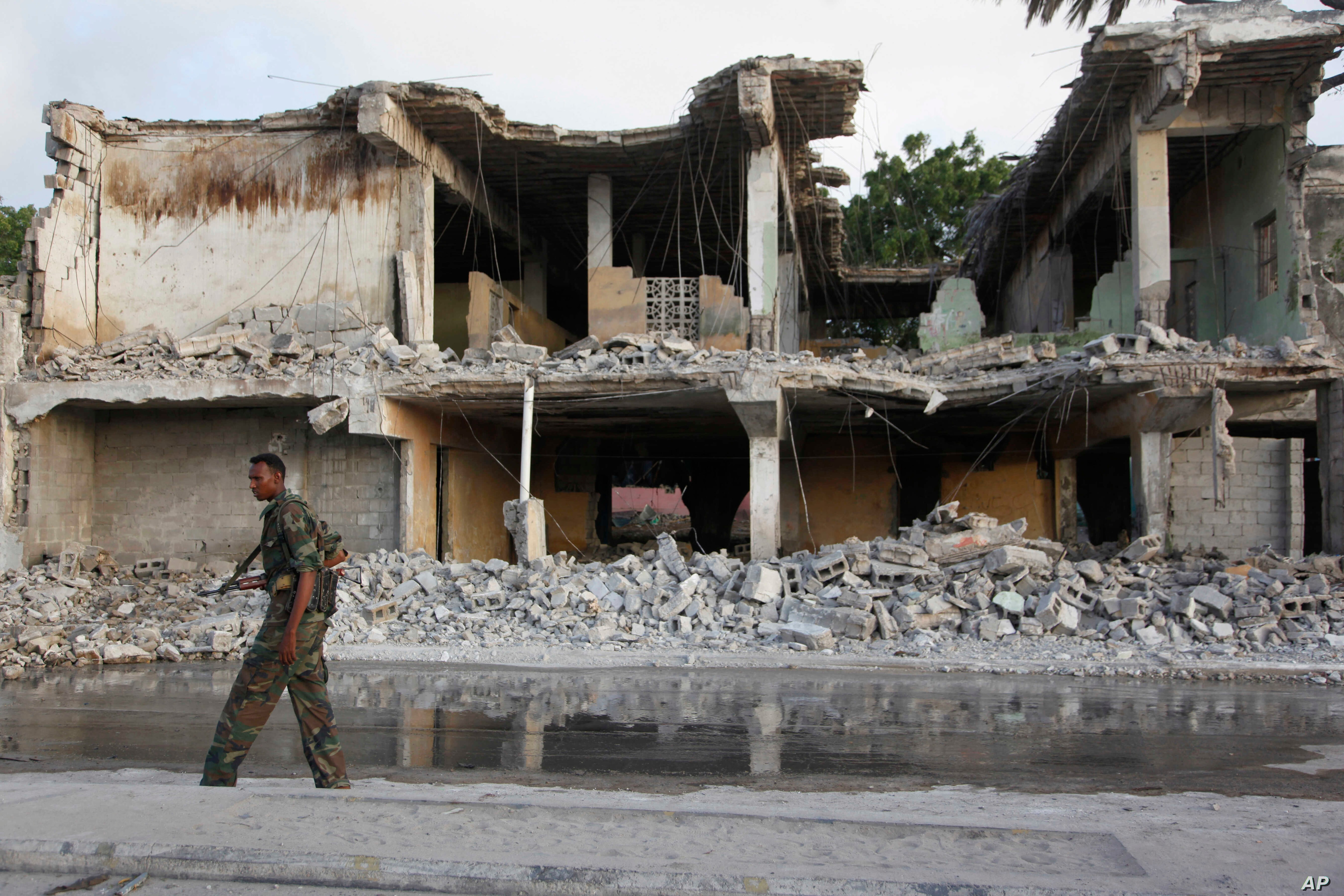 A Somali soldier walks near destroyed buildings, Feb. 27, 2016 after a suicide car bomb on Friday night in Mogadishu, Somalia.