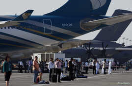 FILE - Visitors watch the flying display during the first day of the Dubai Airshow, November 2011.