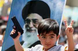 An Iraqi boy living in Iran holds a toy gun, flashes a victory sign in front of a poster of the Iranian Supreme leader Ayatollah Ali Khamenei in demonstration against Sunni militants of the al-Qaida-inspired Islamic State of Iraq and the Levant, Tehr...