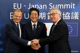 FILE - Japan's Prime Minister Shinzo Abe, center, is welcomed by European Council President Donald Tusk, left, and European Commission President Jean-Claude Juncker at the start of a European Union-Japan summit in Brussels, Belgium July 6, 2017.