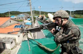 South Korean army soldiers aim their machine guns as they search for a conscript soldier who is on the run after a shooting incident in Goseong, June 22, 2014.