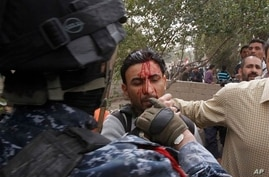 Iraqi officer, left, hits, detains journalist Mohammed al-Rased, center, during a demonstration in Basra, March 4, 2011 (file photo).