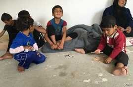 Iraqi refugee children who fled IS with their families playing on the concrete floor of their new home in a camp outside Makhmour, Iraq, April 11, 2016. (S. Behn/VOA)