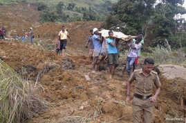ATTENTION EDITORS - VISUAL COVERAGE OF SCENES OF INJURY OR DEATHVillagers carry a dead body after a landslide at the Koslanda tea plantation in Badulla October 29, 2014. A landslide in hilly south-central Sri Lanka is believed to have killed more tha...
