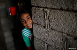 Nine-year-old Iraqi girl Meriam looks out as she stands inside a house, east of Mosul, Iraq July 28, 2017. Picture taken July 28, 2017.