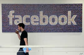 FILE - A Facebook employee walks past a sign at Facebook headquarters in Menlo Park, California. Britain's information commissioner tells BBC on Tuesday she is also investigating Facebook and has asked the company not to pursue its own audit of Cambr