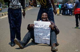 An opposition protester holds a placard denouncing electoral commission officials, at a demonstration in downtown Nairobi, Kenya, Sept. 26, 2017.